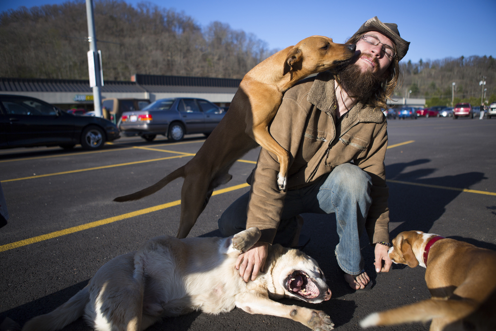 Amigo the dog licks Spiral's face as he returns to their van in a shopping center parking lot in Athens, Ohio. Spiral has permanent residence in California, but spends several months out of the year traveling to the east coast and then back to California in an RV. There are six dogs total that travel with Spiral and his companions.
