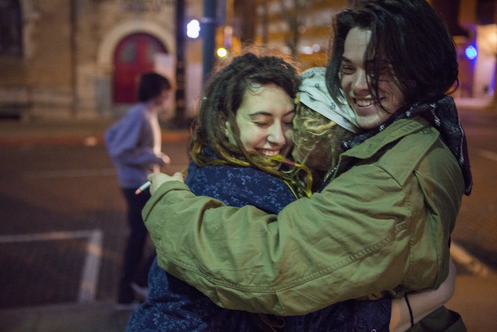 Kima, Solar, and Riley hug while Spiral and others play music on Court Street in Athens.