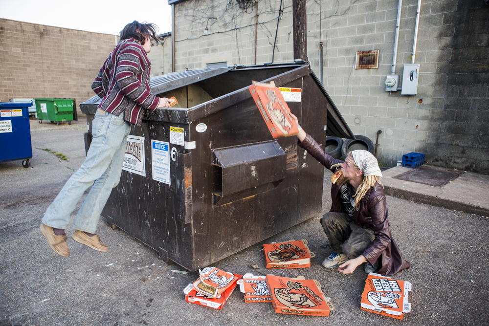 Riley Gates, left, and Solar, right, dumpster dive for Little Caesers pizza behind the shop in Athens, Ohio. The travelers don't stop at typical restaurants or grocery stores for food, but find most of it by dumpster diving and finding food. Their trailer was full of bags of nachos at the time, found in a gas station dumpster and only slightly expired.