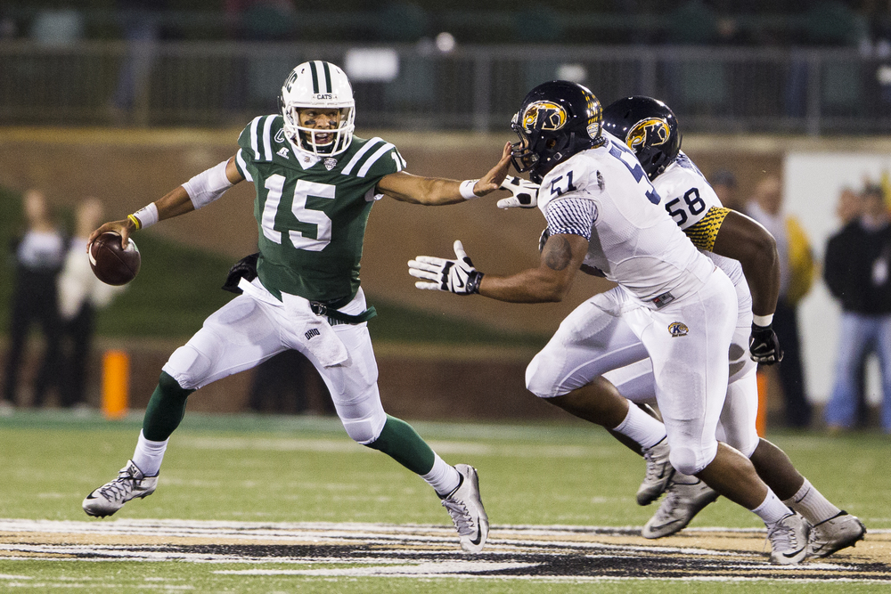 Ohio University redshirt senior quarterback Derrius Vick wards off Kent State defenders Terence Waugh and Theo Eboigbe at Peden Stadium on Nov. 11, 2015. Ohio won 27-0.