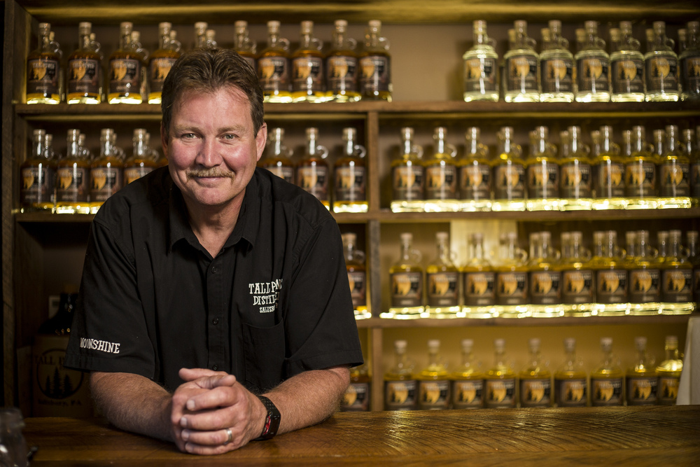 Tall Pines Distillery co-owner Keith Welch stands for a portrait in front of some of the distillery's moonshine in Salisbury, Somerset County, on Monday, July 11, 2016. The distillery claims to be the first legal moonshine distillery in Somerset County since Prohibition.