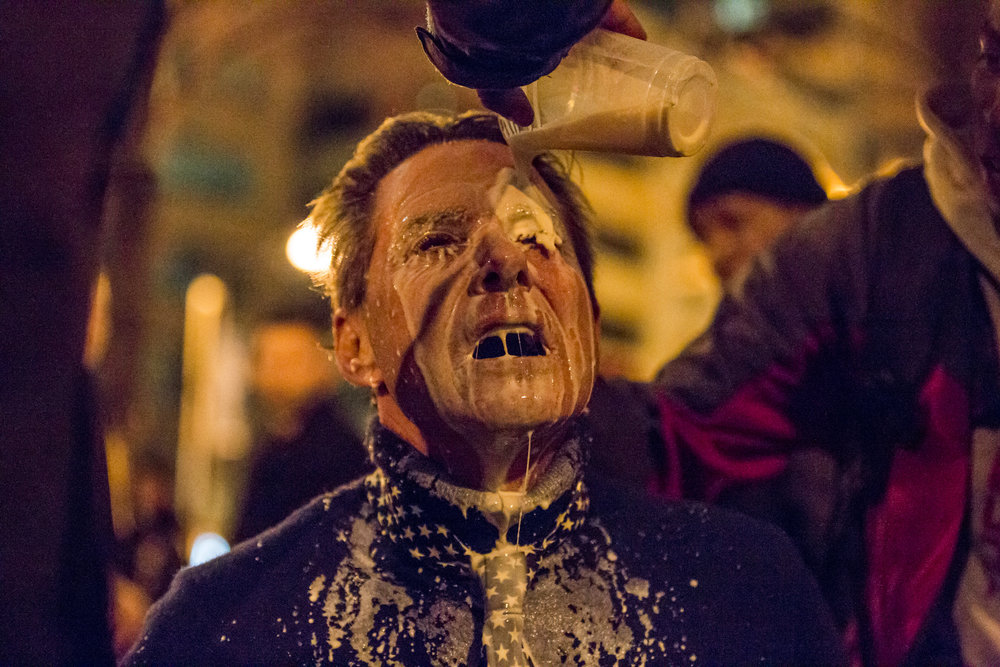 Protesters help pour milk into the eyes of Jeff Leonard, a Trump supporter from Las Vegas who was pepper sprayed.