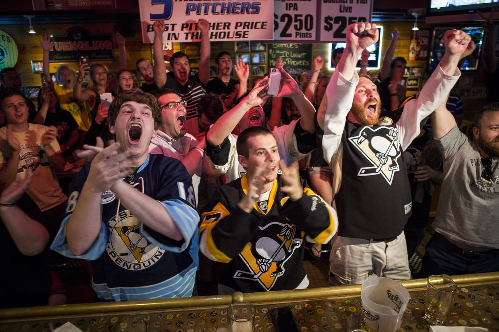 John Firestone, left, Evan Wright, center and Brent Krysinski celebrate as the Penguins won game six and the Stanley Cup at Hemingway's Cafe in Oakland on Sunday, June 12, 2016.