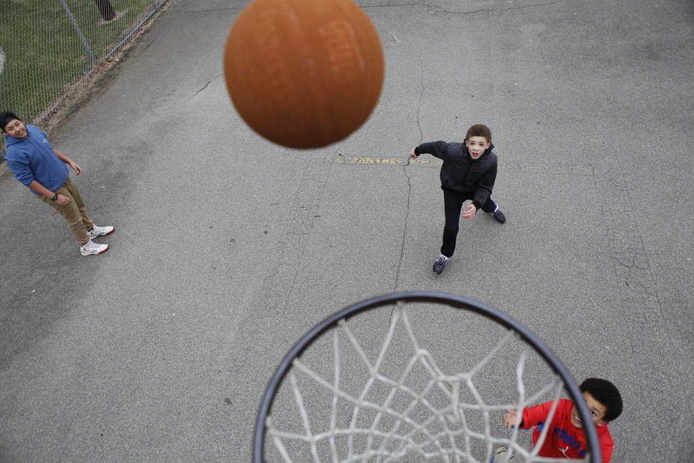 Teenagers play basketball on an unseasonably warm December day in Jeannette, Pennsylvania.