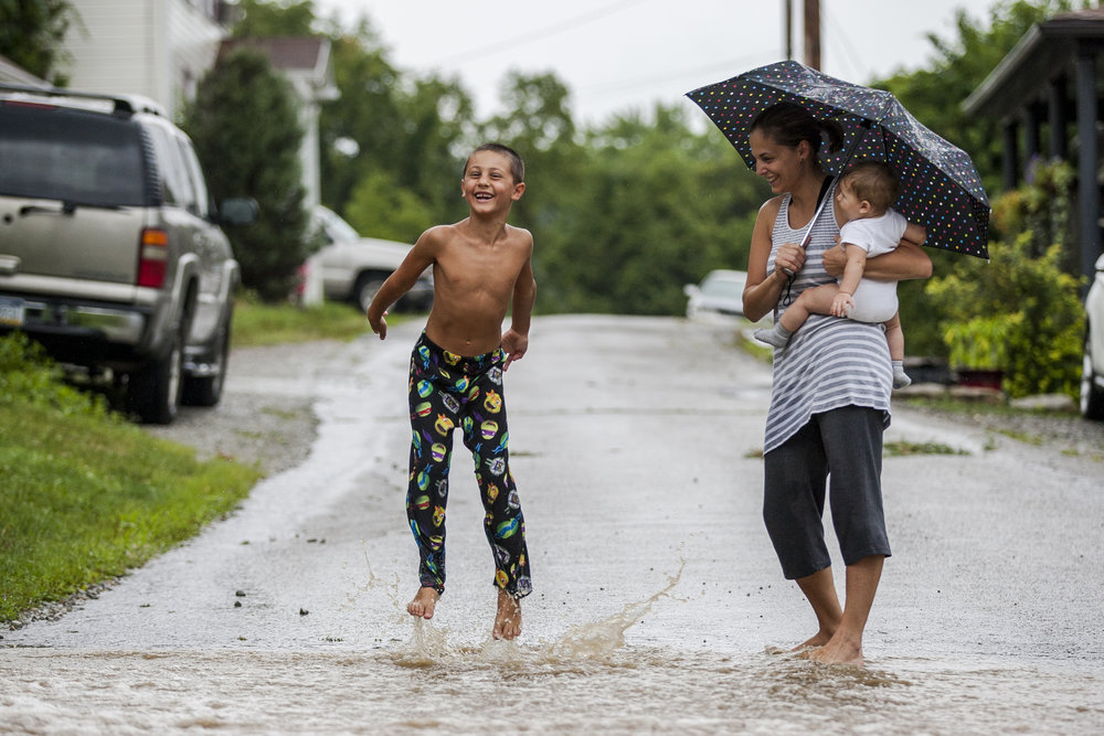 Robert Repovz, 6, splashes through rain water running across First Street while his mother Anita and baby sister Gabriella watch in New Stanton, Pennsylvania, on Saturday, July 30, 2016.