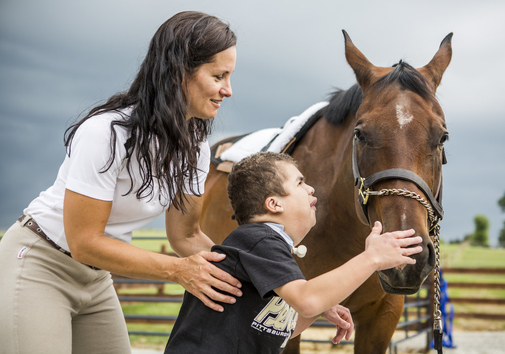 Mason Markosky pets Sleepy the horse after riding while being held by his mother Catherine, owner of Southern Tier Alternative Therapies (STAT), at the Ligonier Theraputic Center in Cook Township, Pennsylvania, on Monday, July 18, 2016. Mason has a rare condition called Costello Syndrome and couldn't sit up or walk until he tried hippotherapy.