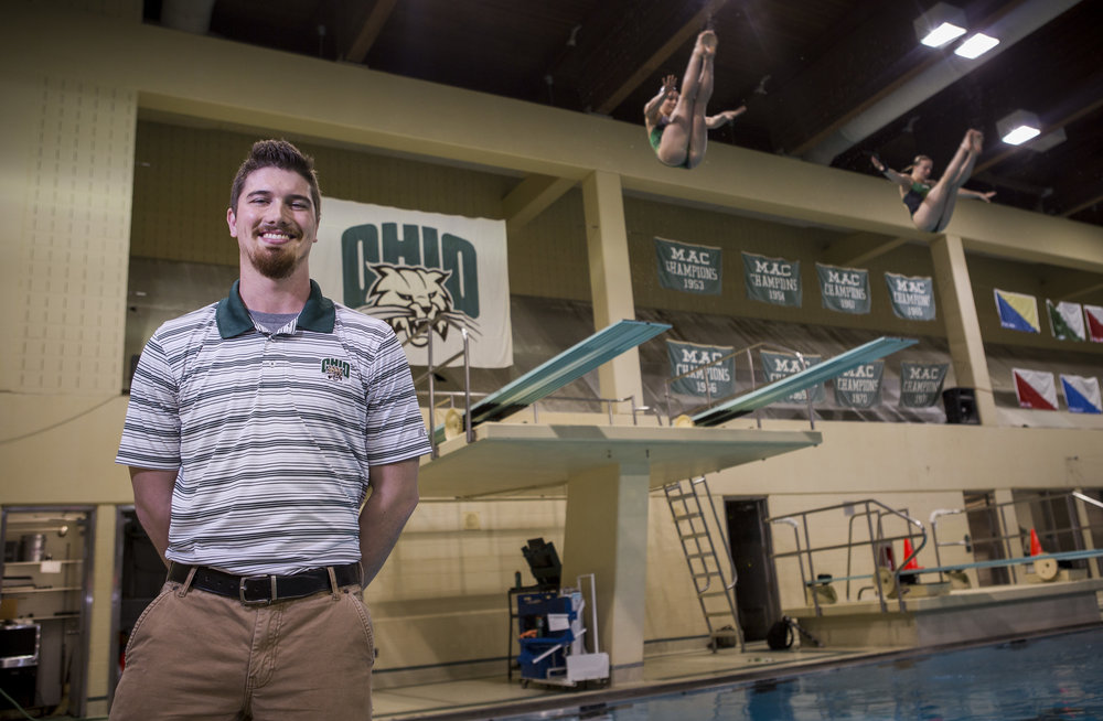 Tom Gimm, the new head diving coach, stands for a portrait as Ireland Littlejohn and Olivia Dillon dive in the background at the Ohio University Aquatic Center on Thursday, Jan. 26, 2017.