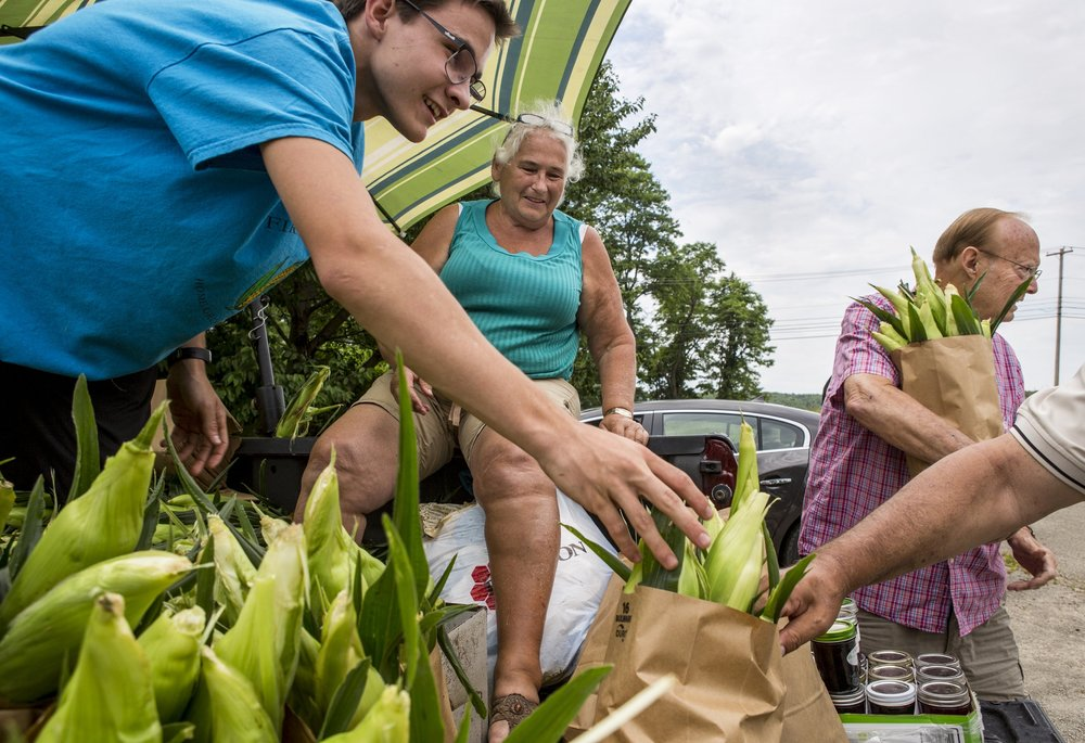 Rita Firestone of Greensburg and her assistant of four years, Jacob Porch, sell corn to customers along Route 30 in Latrobe, Pennsylvania, on Friday, July 1, 2016. Firestone has been selling corn, flowers, pumpkins and the like at the same spot for 46 years.