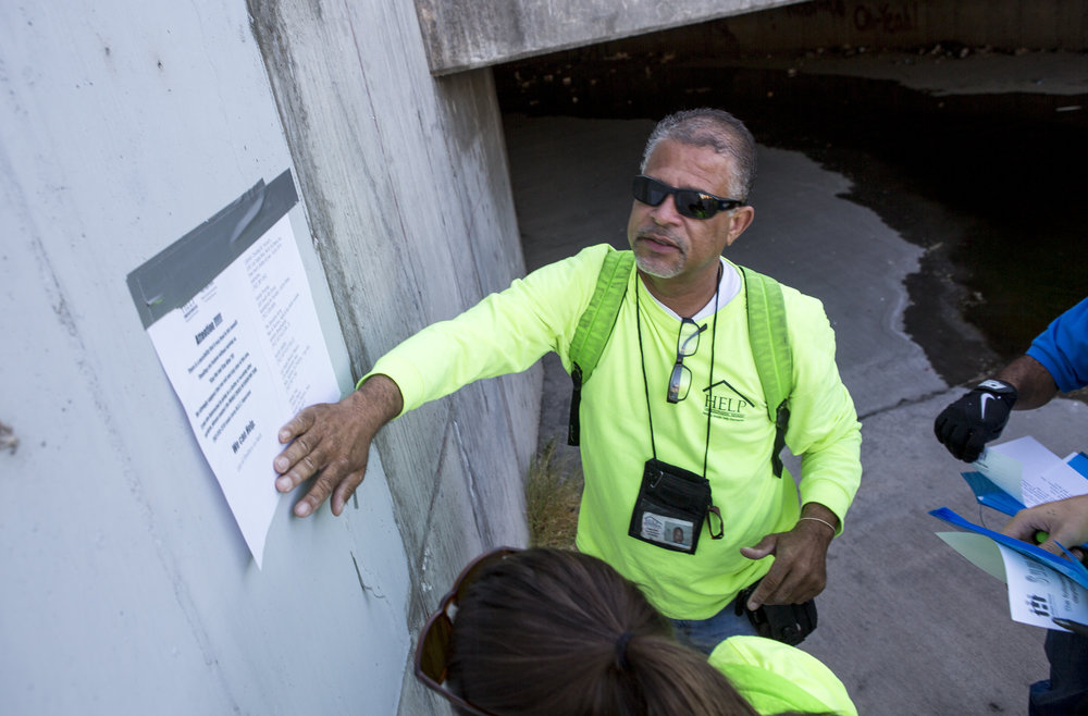HELP of Southern Nevada employee Louis Lacey, the Mobile Crisis Intervention Team manager, puts up a sign warning the homeless about upcoming rain in monsoon season near flood tunnels under the Hard Rock Hotel and Casino on Tuesday, June 27, 2017.  Patrick Connolly Las Vegas Review-Journal @PConnPie