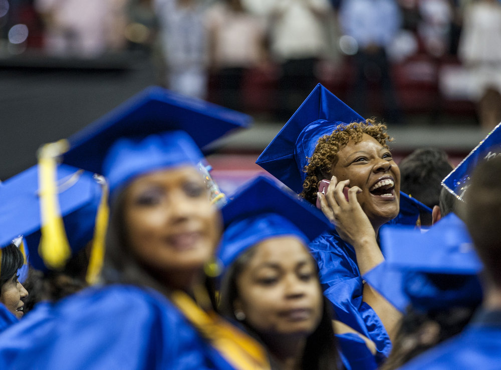 A College of Southern Nevada graduate talks with an audience member on the phone before the start of commencement at the Thomas and Mack Center in Las Vegas on Monday, May 15, 2017.