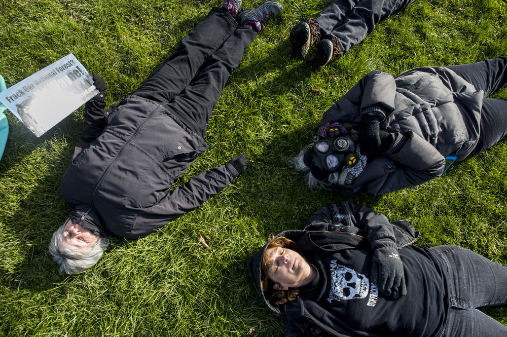 "Protesters lay outside of the Wayne National Forest Headquarters during a ""die-in"" to demonstrate against the auction of Wayne land for fracking along Route 33 in Athens County, Ohio, on March 23, 2017."