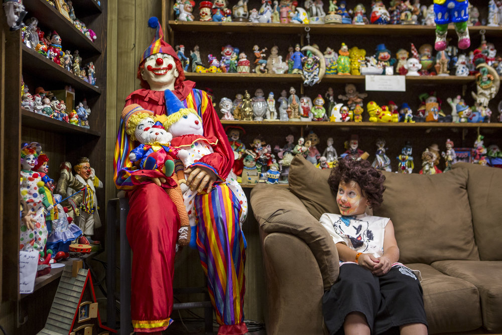 "Kai James, 9, glances over at the life-size clown known as ""Mr. Creepy"" in the lobby of the Clown Motel in Tonopah, Nevada, on Tuesday, July 25, 2017. James came with his brother and mom from Las Vegas to stay for a night and dressed up in clown attire."