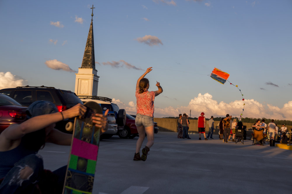 A woman twirls her kite as the sun sets during a rooftop concert in Athens, Ohio, on April 27, 2017.