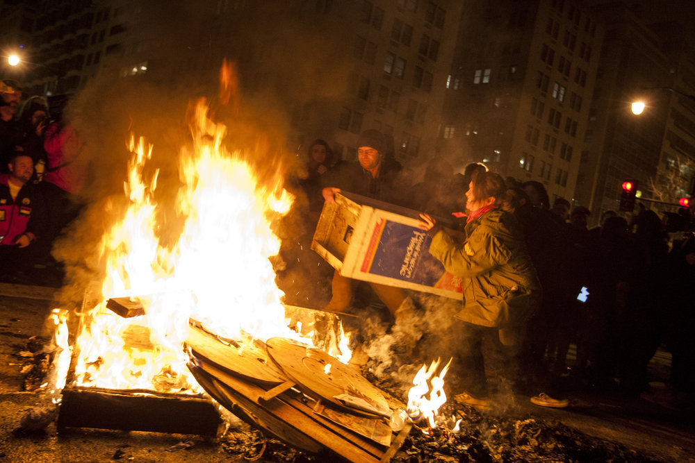 Protesters throw a newsstand on a fire near the intersection of K and 14th streets in Washington, D.C., following the inauguration of Donald Trump on Jan. 20, 2017.