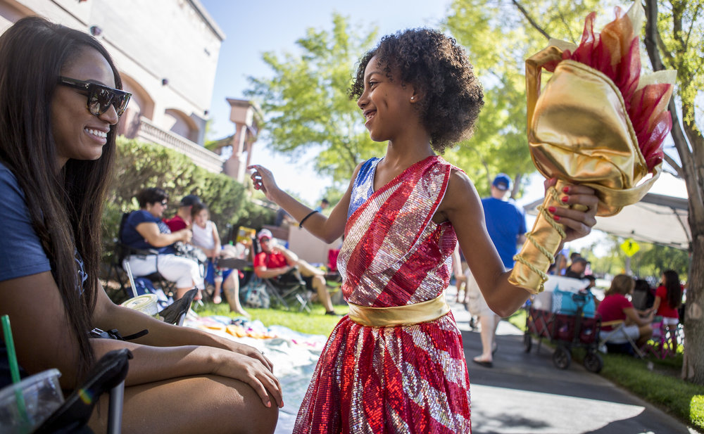 Brooklynn Winslow, 8, shows off her sparkly American flag dress and torch while her mother Natalie Winslow smiles during the Summerlin Council Patriotic Parade in Summerlin, outside of Las Vegas, on Tuesday, July 4, 2017.
