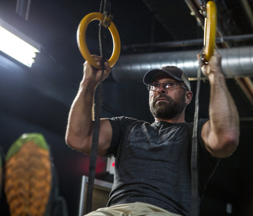 "Jamie Betit pulls himself up on rings at Powerpit 24. Despite his appearance, he doesn't have the personality of most other ""gym bros."""