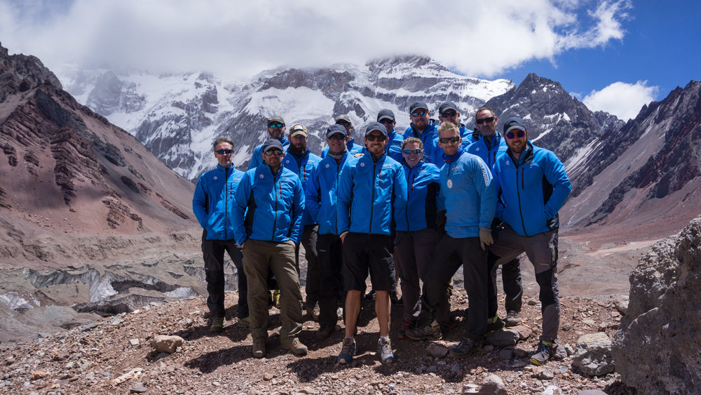 The imposing south face of Aconcagua looms behind the team.
