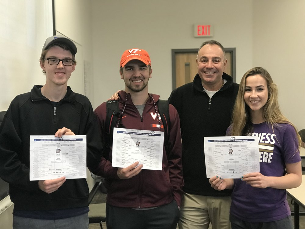 Virginia Tech freshman Evan McNally (l), junior John Cogsdale, and freshman Rosie Hutchison (r) . display their 2018 NCAA Tournament brackets with Bill Roth this past Tuesday afternoon.