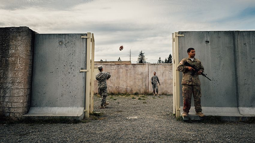 1st place in the Sports Photography category: Two soldiers play catch with a football while a fellow soldier watches the perimeter of the training grounds during the Expert Field Medic Badge course at Joint Base Lewis-McChord, Wash., Sept. 24, 2015. The EFMB is the non-combat equivalent of the Combat Medical Badge and is awarded to medical personnel of the U.S. military who successfully complete a set of qualification tests. IMAGE: SENIOR AIRMAN JORDAN A. CASTELAN, USAF