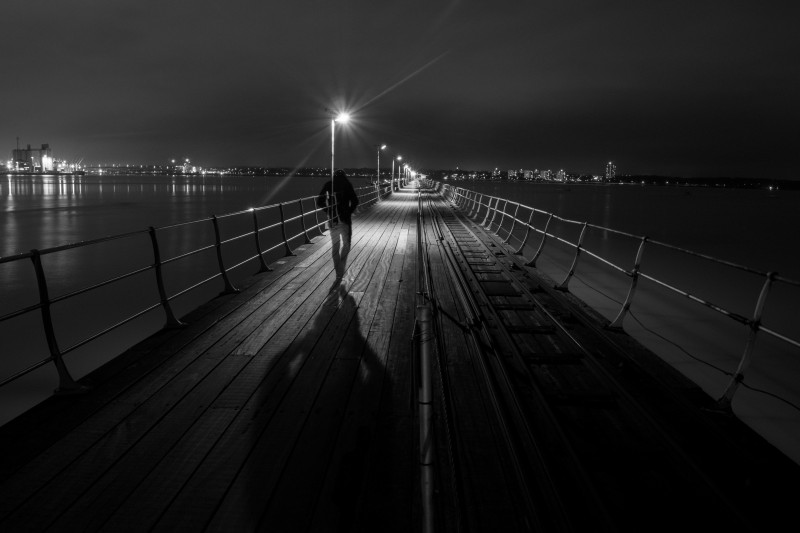"This photo is called ""THE LONELY COMMUTER - HYHE PIER"" and was taken by  Jamie Percy . She said, ""I've chosen one of my proudest pieces for World Photo Day. I created this long expo ""the lonely commuter"" for a college project using my 18-50mm lens, remote shutter on 10 second delay, f10 with SS 13, ISO 200 and me as the model! This image brings back those emotions felt on that long and lonely walk in those cold, dark early winter mornings. It has personal meaning and I'm please to say now hangs in the gallery at Southampton City College."""