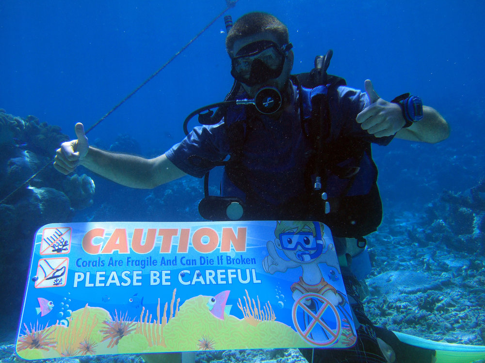 Romain Vivier (in the photo behind the sign) chose the path to progress.  While a student at James Cook University, he designed and developed five of these underwater signs as part of a research project. The signs were placed in areas where visitors were likely to walk on and break fragile corals. His research proved that these signs did significantly affect visitor behavior. Such signs are a good idea for popular coral reef sites were visitors might not be familiar with corals, let alone about their fragility. These signs have the potential to maintain a site in good conditions, therefore allowing sustainable tourism.