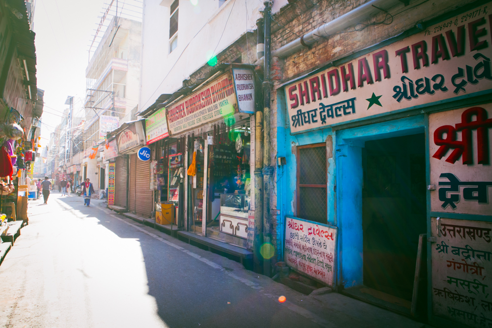 A half empty street, with vendors just opening their shops in the morning.