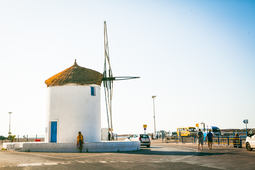 Greece's iconic windmill greeting visitors arriving into the port! A lot of people sit around the base while they wait for their ferry.