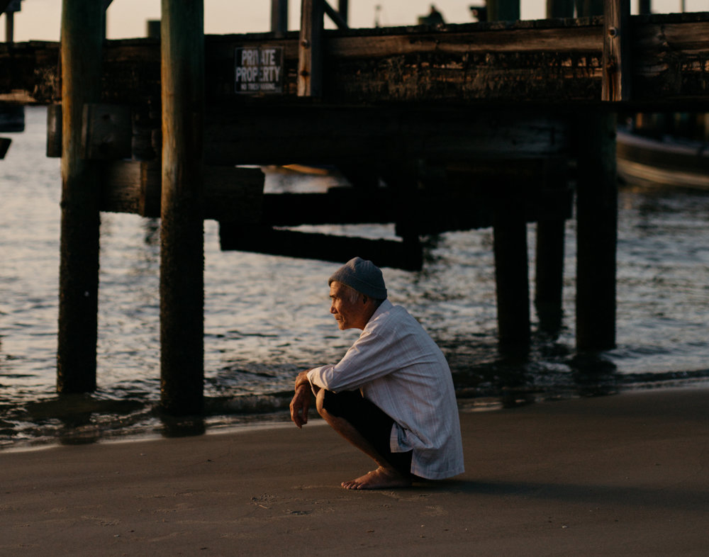 I was doing a shoot at the beach when I spotted this man watching the sunset. The time between me noticing him and snapping the shot was probably less than 2 seconds. Didn't even look through the viewfinder, just shot from the hip since I didn't want to be obvious. I was lucky enough to get it in focus.