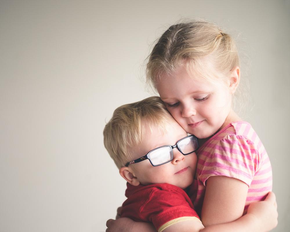 Siblings cuddle cute kids