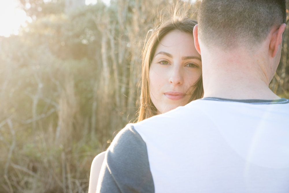 Engaged couple looking over guys shoulder with golden light from behind