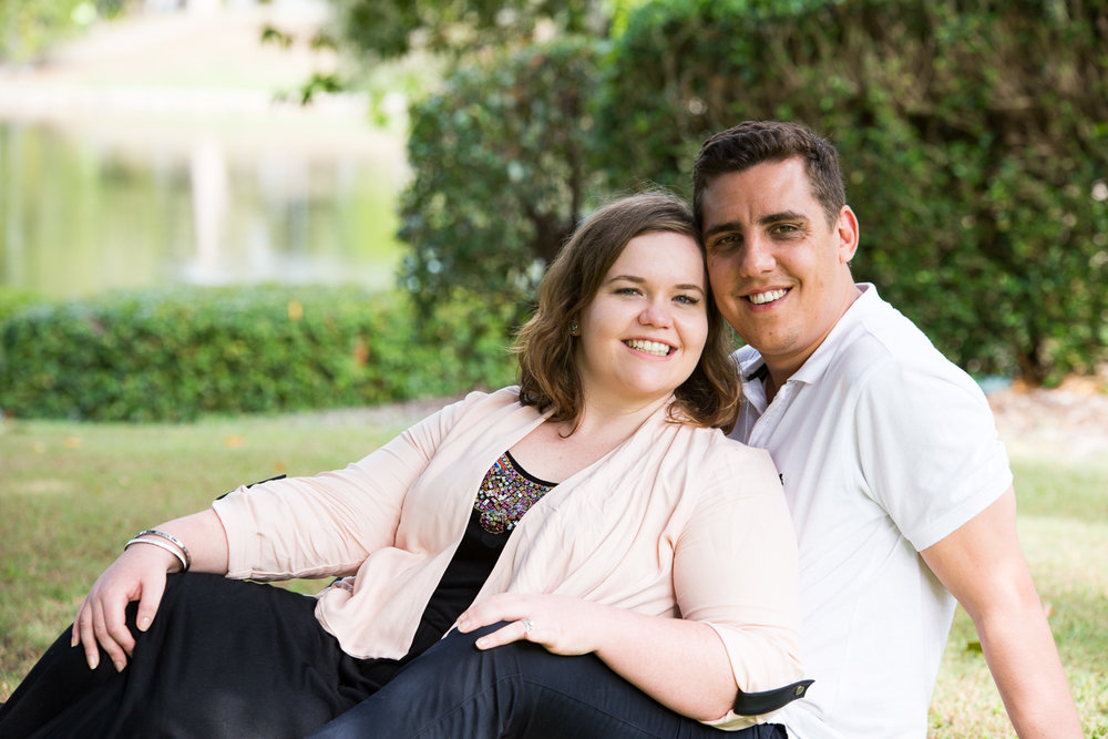 Outdoor portrait of young married couple sitting in park