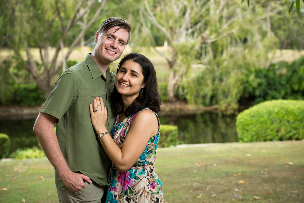 Outdoor portrait of engaged couple with green park background