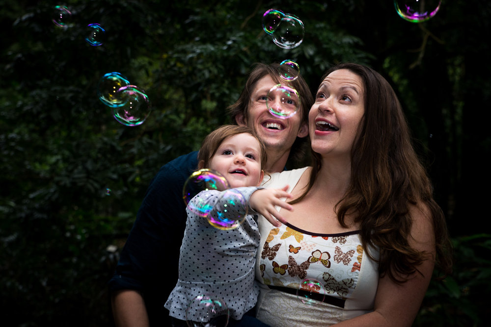 mum, dad and daughter catching bubbles