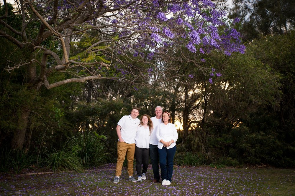 Adult family portrait at dusk under jacaranda tree