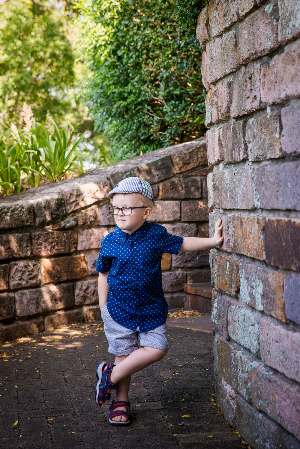 Boy leaning against rock wall in cottage garden