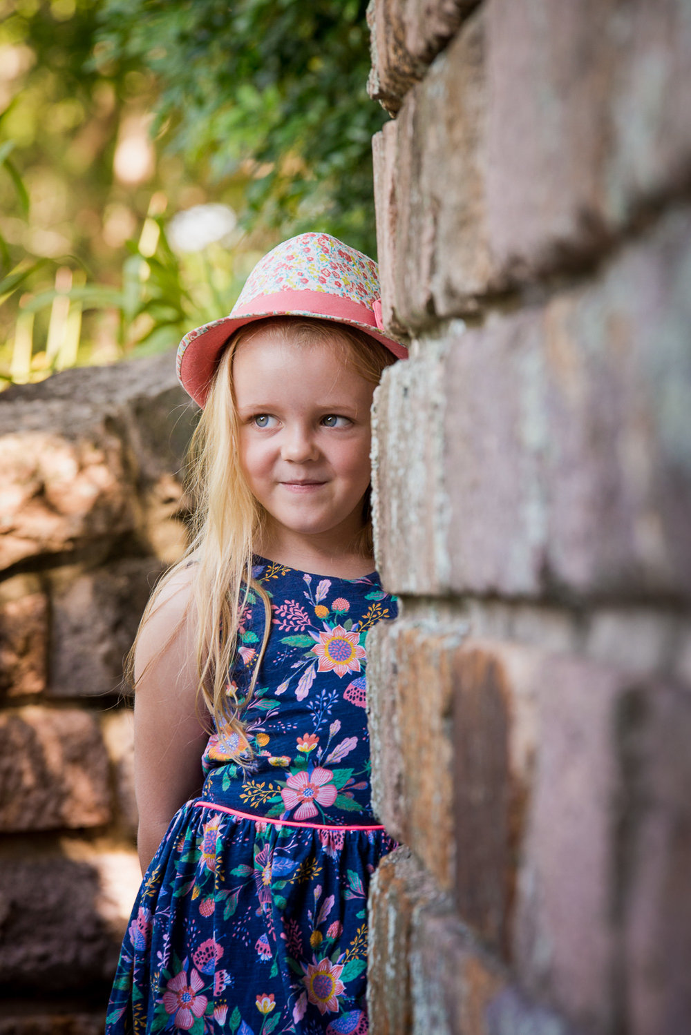 Girl leaning against rock wall in cottage garden