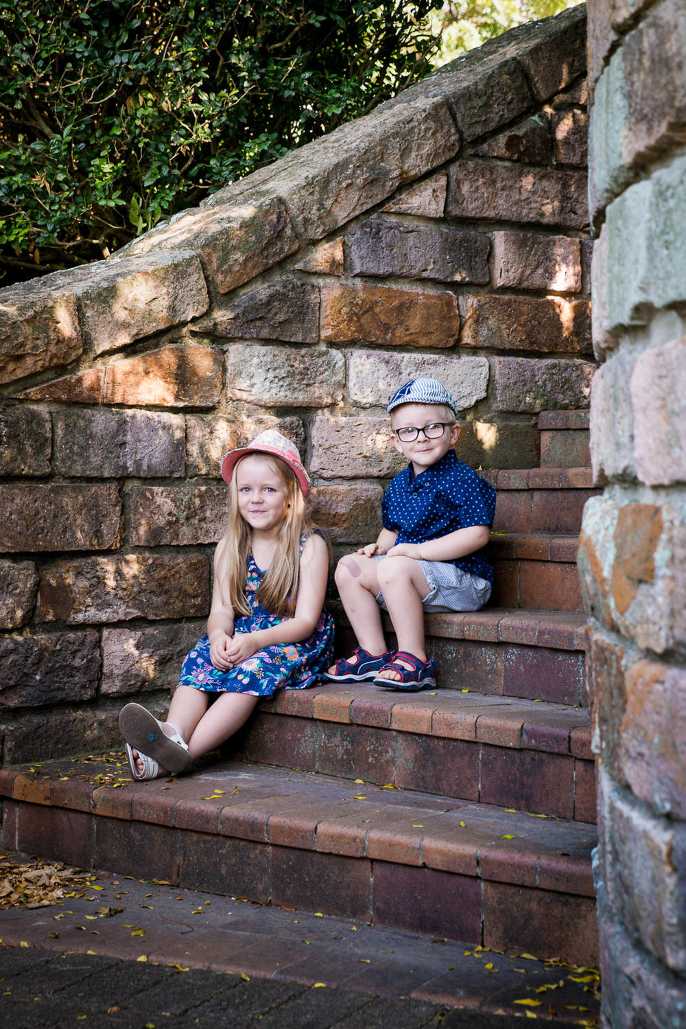 Boy and girl sitting on steps in amongst cottage garden