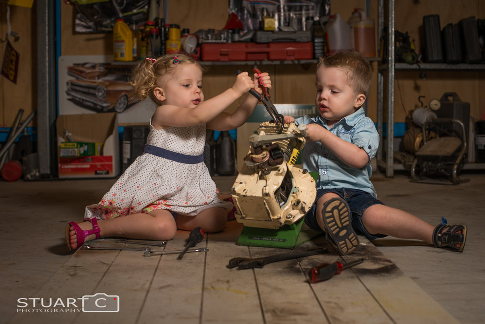 Children playing fixing an engine in the garage