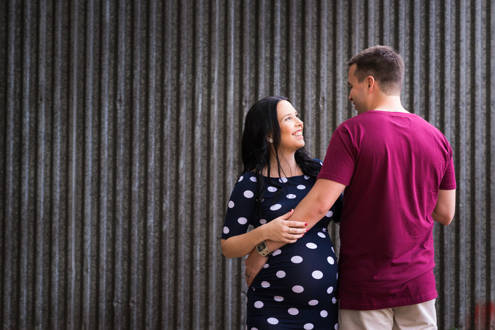 Maternity portrait in urban scene of couple standing in front of tin wall in Caboolture