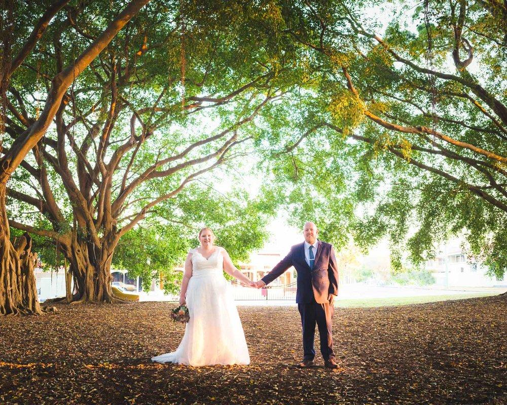 Bride and Groom in centre under huge fig tree canopy at Wedding ceremony in Wirreanda Park in Buderim