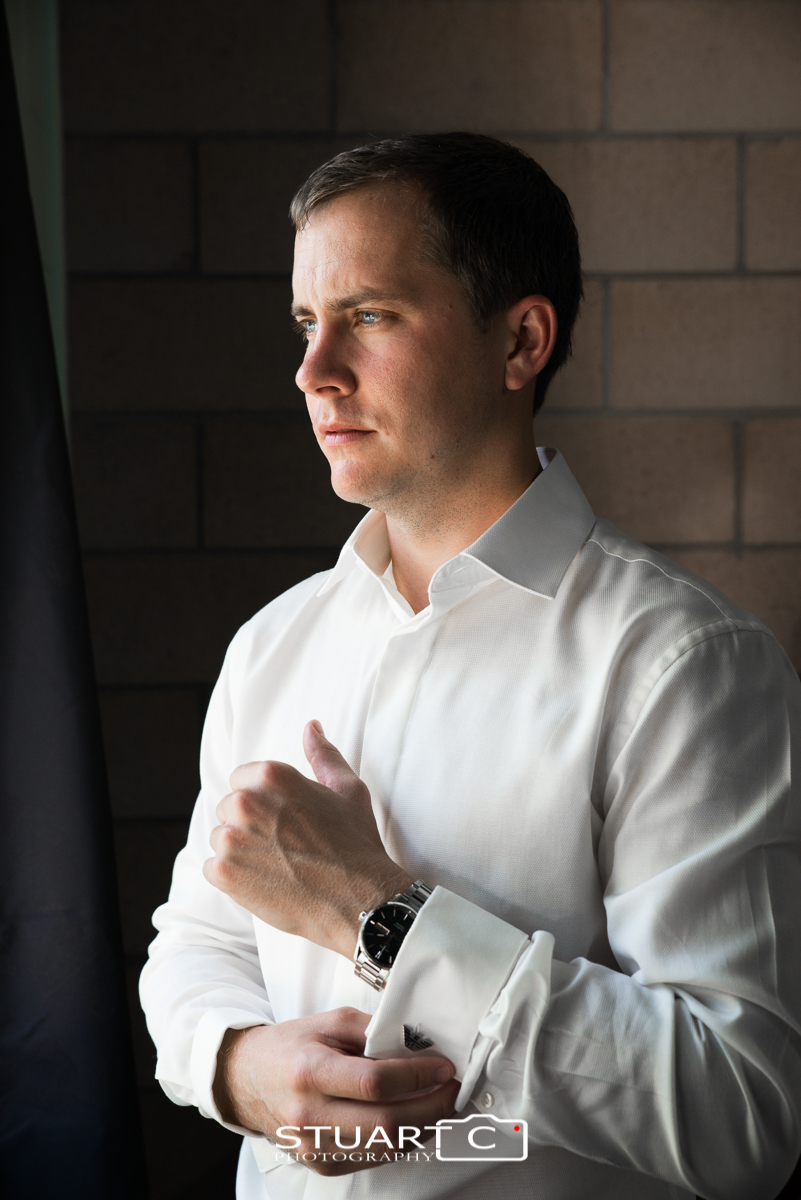 Groom wearing white shirt buttoning his cuff in soft window light