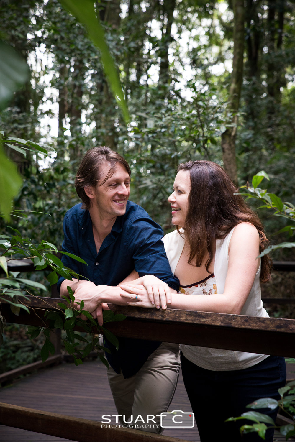 Engaged couple leaning against handrail in rainforest at Mary Cairncross Reserve Maleny Sunshine Coast Hinterland