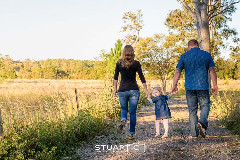 family walking down dirt road in bushland rural setting