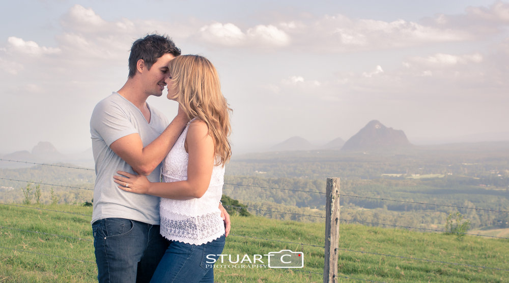 engaged couple in rural setting with glass house mountains behind