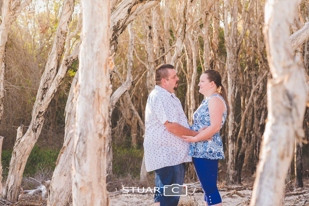 engaged couple wearing white and blue in amongst paper bark trees at beach