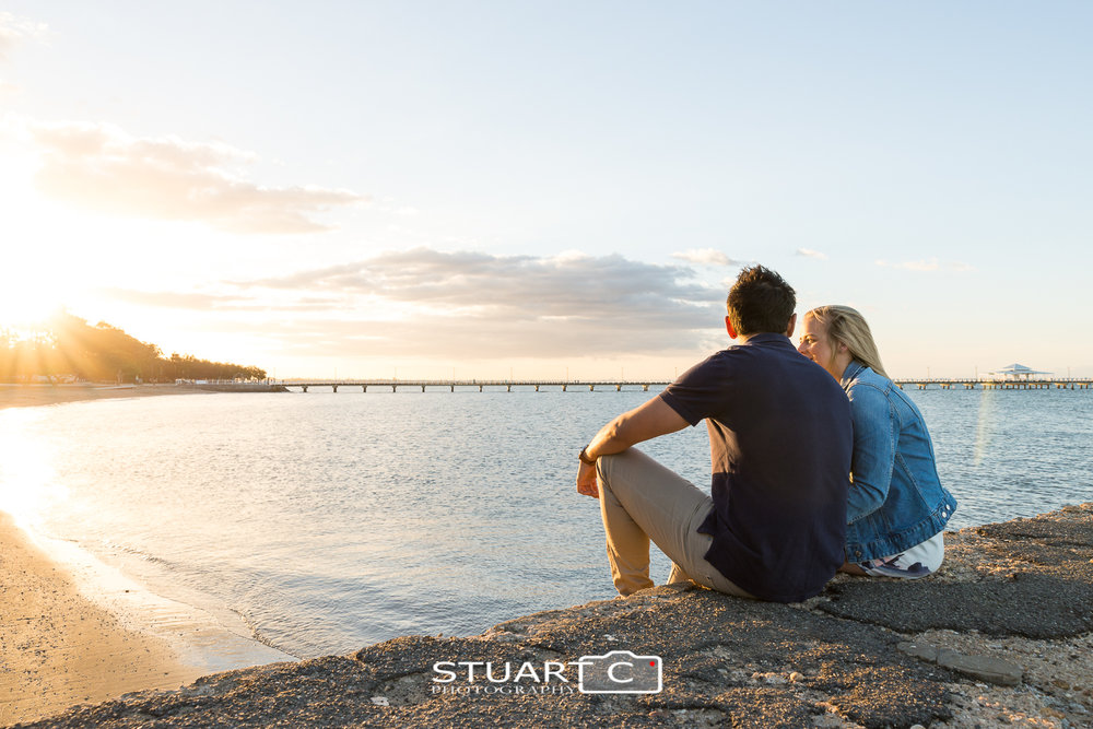 engages couple sitting on pier watching sunset at shorncliffe