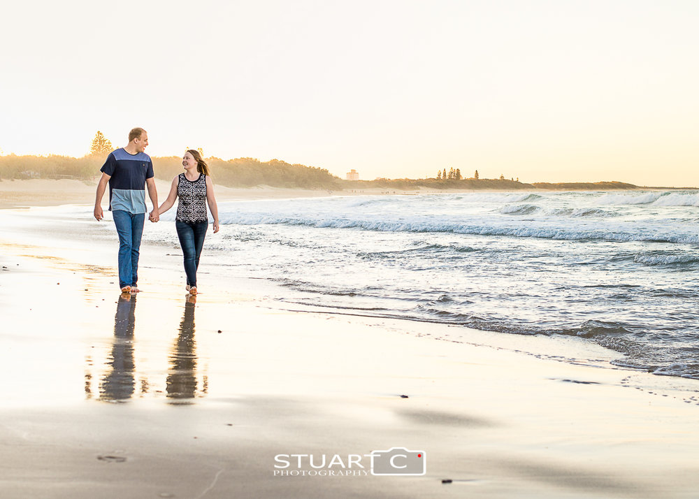 engaged couple walking along dicky beach caloundra at sunset