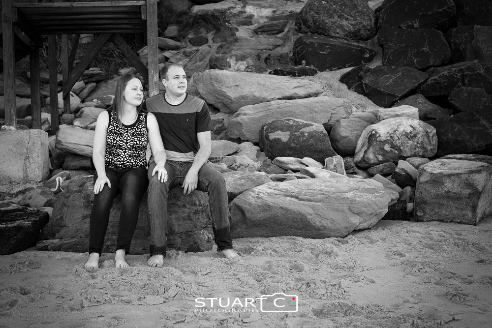 engages couple sitting on rocks at beach in black and white