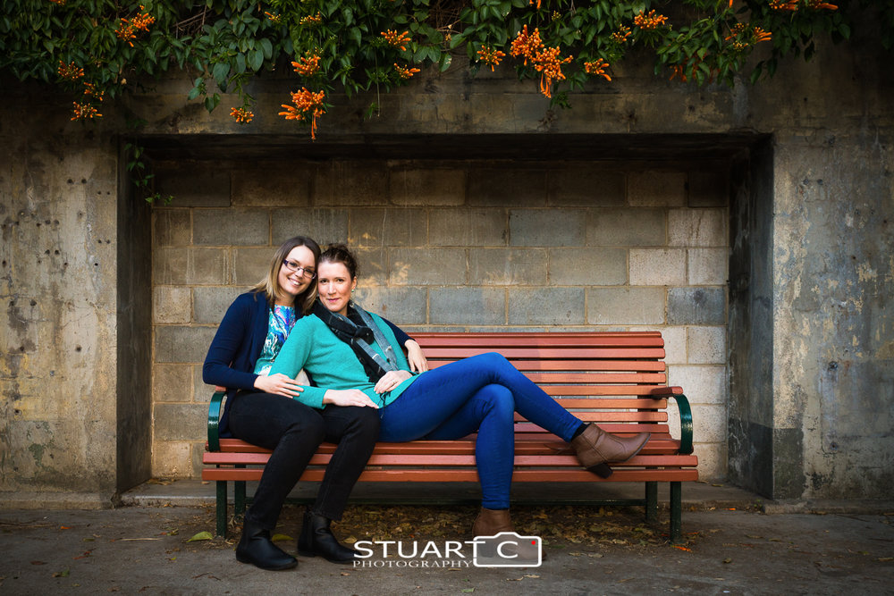 female couple sitting on park bench in front of block wall with vines above