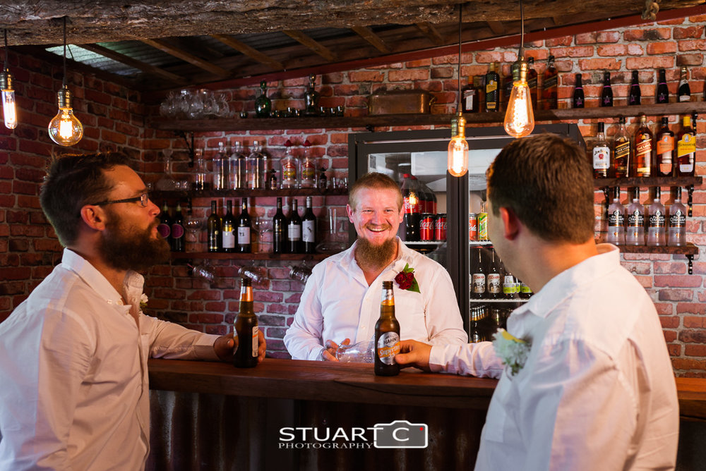 Groom and Groomsmen at the home bar inside rustic barn before home wedding at Elimabah